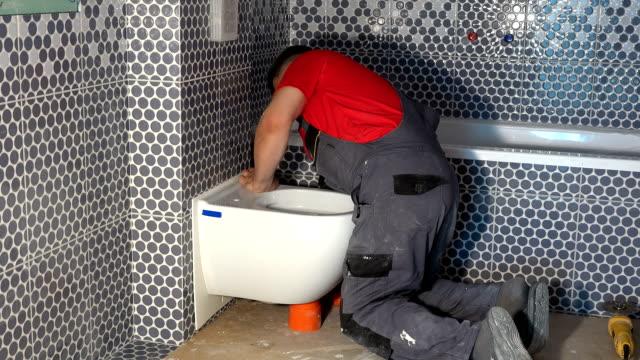 Professional plumber man install toilet bowl pan in new modern bathroom