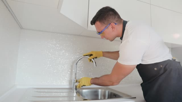 A professional plumber worker, in uniform, assures the quality of the installation of the crane in the kitchen. Installing a new faucet on kitchen wash basin A professional plumber worker, in uniform, assures the quality of the installation of the crane in the kitchen. Installing a new faucet on kitchen wash basin kitchen sink stock videos & royalty-free footage