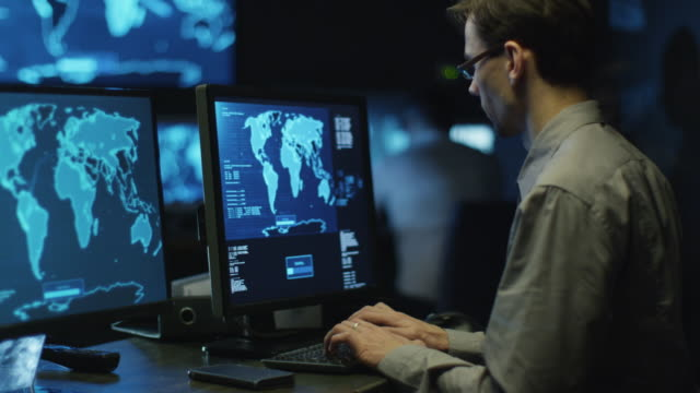 IT professional programmer in glasses is working on computer in cyber security center filled with display screens. video
