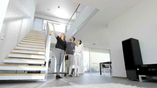 professional real estate agent shows stylish modern house to a beautiful young couple. - mostrare video stock e b–roll