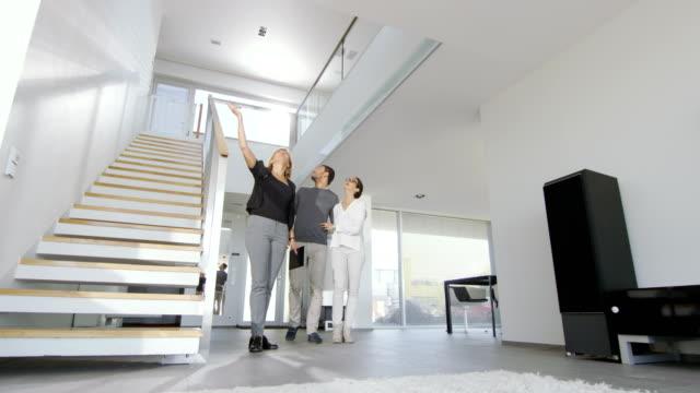 Professionelle Immobilienmakler zeigt stilvolles moderne Haus, ein schönes junges Paar. – Video
