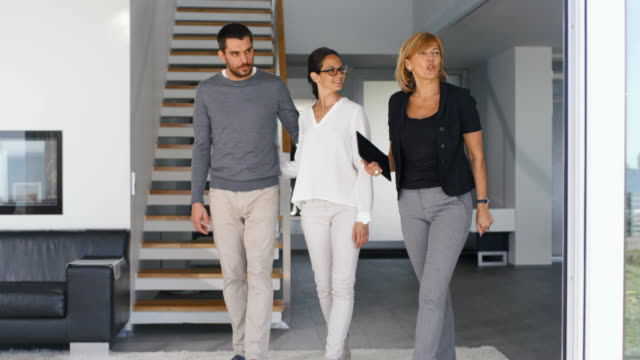 Professional Real Estate Agent Shows Stylish Modern House to a Beautiful Young Couple Who are in the Market for Purchasing/ Renting New Home. House is Modern, Stylish and Bright.