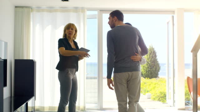 Professional Real Estate Agent Shows Stylish Modern House to a Beautiful Young Couple Who are in the Market for Purchasing/ Renting New Home. House Has Floor to Ceiling Windows and Seaside View. video