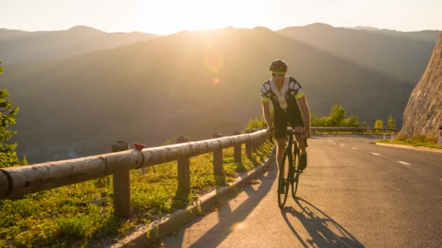 Professional road cyclist illuminated by sunlight, pedaling uphill standing up at sunset