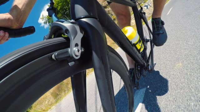 professional road cyclist speeding downhill on a mountain road - ciclismo su strada video stock e b–roll