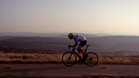 Professional road cyclist Side view of professional road cycling outdoor, he riding at sunset. determination stock videos & royalty-free footage