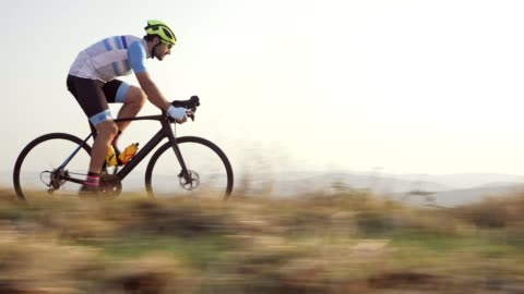 Professional road cyclist Side view of professional road cycling outdoor, he riding at sunset. endurance stock videos & royalty-free footage