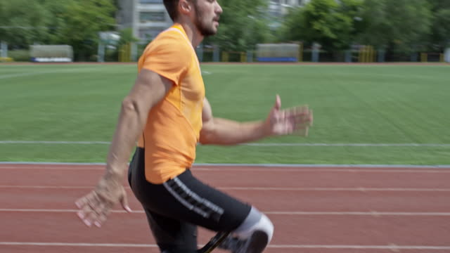 Professional Runner with Artificial Leg Jogging on Stadium Tilt down of handicapped athlete with artificial foot running on stadium track in slow motion amputee stock videos & royalty-free footage