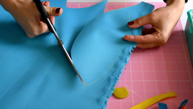 a professional seamstress cuts out the details of clothes from the fabric with scissors - forbici video stock e b–roll