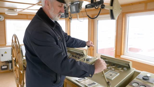 il capitano senior professionista nella timoneria gestisce la nave utilizzando due leve. - leva video stock e b–roll