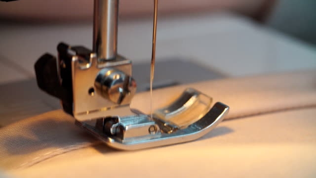 professional sewing machine stitching with white thread an italian haute couture fabric, the seamstress sews a high fashion outfit. concept of industry, tradition, fashion - cucire video stock e b–roll
