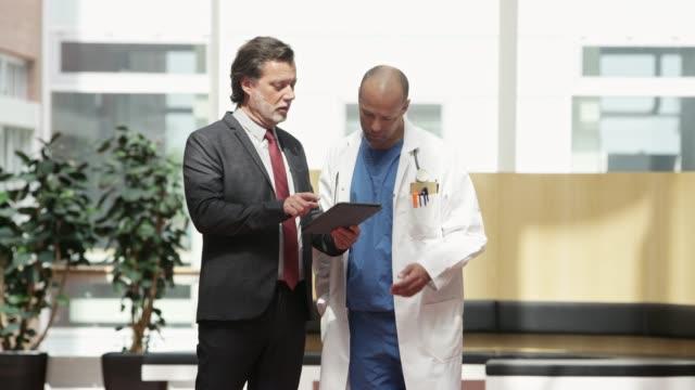 professional showing digital tablet to doctor - praca w sektorze handlowym filmów i materiałów b-roll