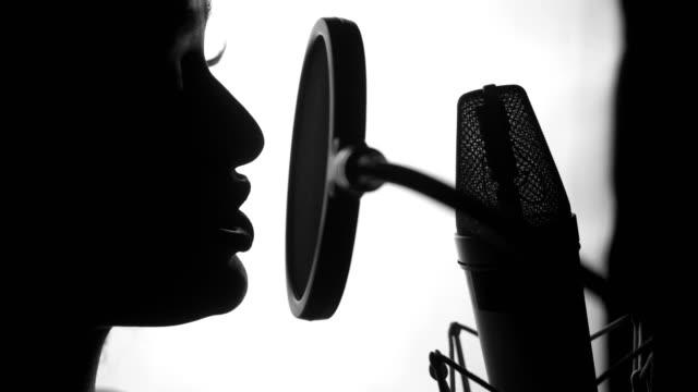 cantante professionista davanti a un microfono che esegue una canzone in studio. - cantante video stock e b–roll
