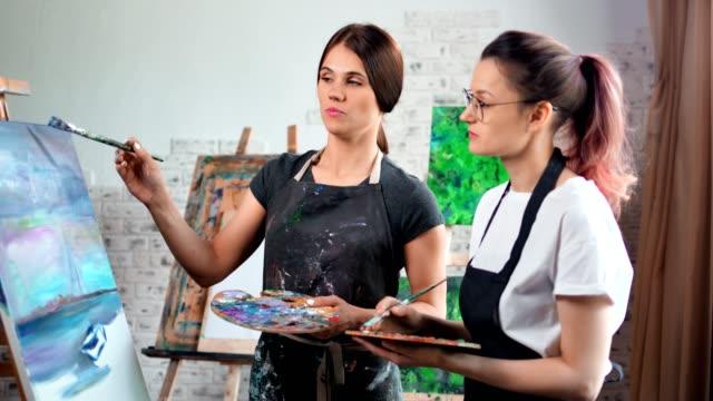 Professional skilled female teacher artist teaching painting young girl at studio medium shot