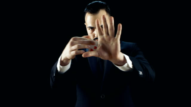 Professional Skilled Magician in a Black Suit Performs Card Disappearance and Appearance Trick Multiple Times. Sleight of Hand.Background is Black. video
