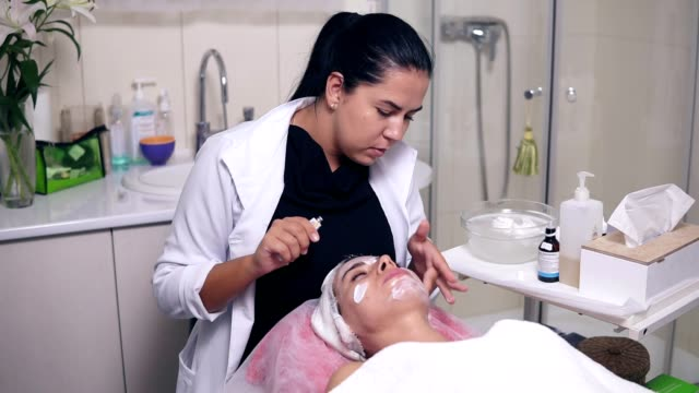 Professional skin care for young woman in spa salon. Young woman is lying on the couch while professional cosmetologist is apllying special treatment on woman's face