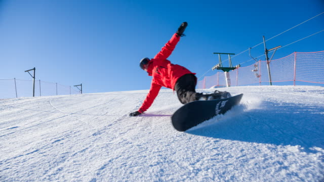 Professional snowboarder making a big turn on ski slope at mountain resort