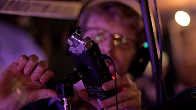 Professional soundman setting up microphone at sound studio, preparing concert video