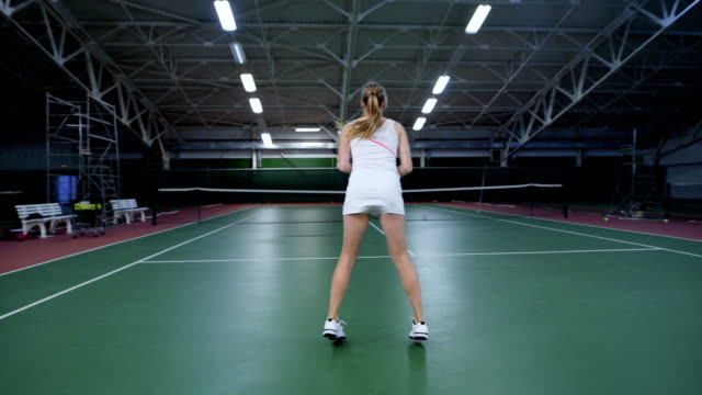 Professional sport players having training at indoor court improving skills. Woman in white sport outfit is jumping and hitting balls with racket. Female instructor teaching man playing tennis video
