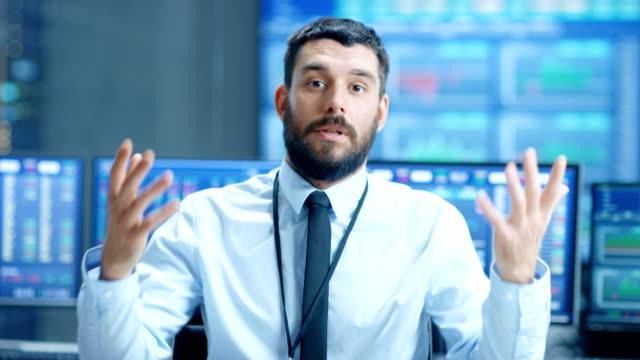 vidéos et rushes de professionnels du marché boursier trader charismatiquement parle à la caméra. derrière lui, les écrans d'ordinateur avec ticker nombres, données, graphiques. - expliquer