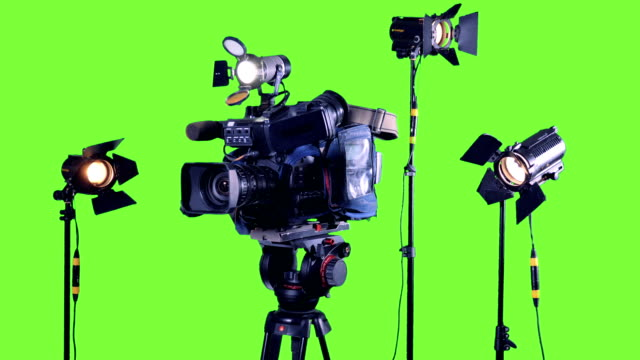 Professional studio spotlights and a professional video camera on a green screen. video