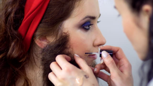 Professional stylist creates a scenic character for young actress Professional stylist creates a scenic character for young actress. She sticks the artificial beard on girl's face using a transparent nail polish. Dressing room in theatre. Prores codec. greasepaint stock videos & royalty-free footage