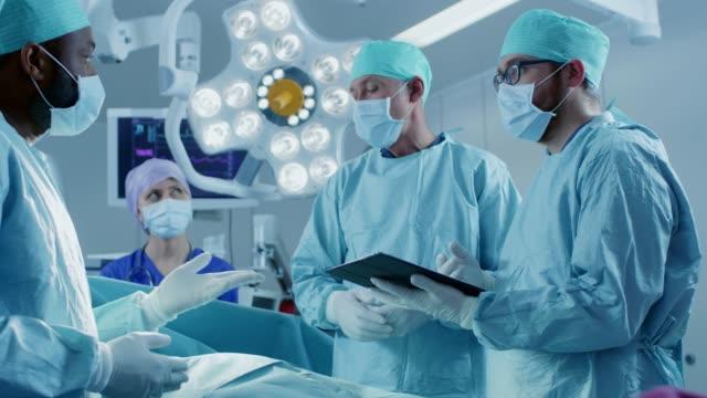 專業的外科醫生和助手在手術中交談和使用數位平板電腦。他們在現代醫院的手術室裡工作。 - surgeon 個影片檔及 b 捲影像
