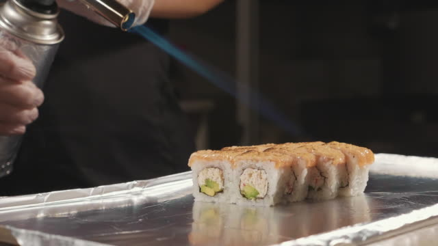 Professional sushi chef preparing roll via fire at commercial kitchen, close-up. video