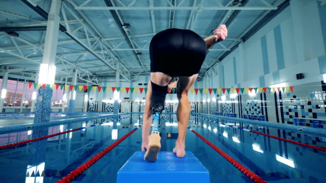 vídeos de stock e filmes b-roll de professional swimmer with prosthesis jumps in a pool, back view. - melhoria