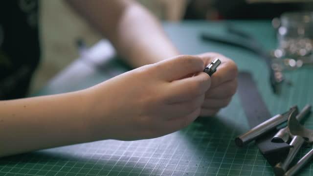 Professional tailor sets buckle into black leather belt
