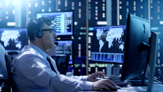Professional Technical Support Personnel Working in a System Control Center. We See Many Working Displays with Various Data Visible on Them.