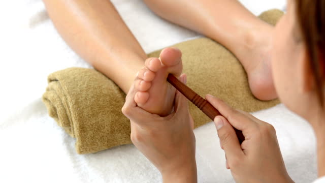 Professional therapist giving traditional thai foot massage with stick to a woman in spa video