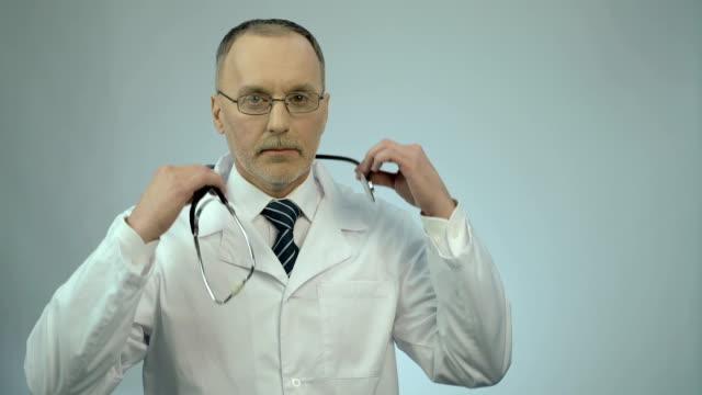 プロのセラピストが患者を診察する準備ができて、首に聴診器 - 首点の映像素材/bロール