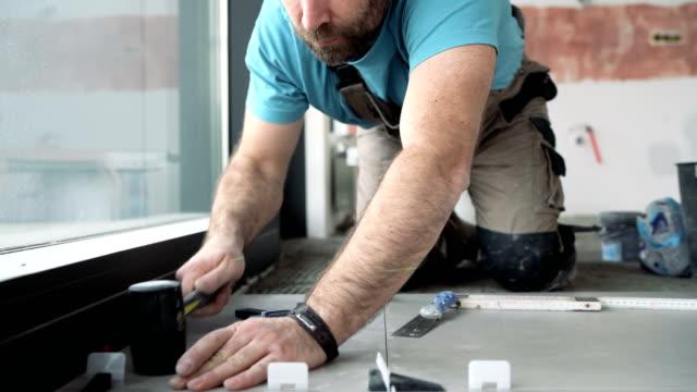 professionella plattsättare som placerar separatorer mellan nyinstallerade plattor - construction workwear floor bildbanksvideor och videomaterial från bakom kulisserna