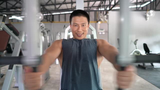 vídeos de stock e filmes b-roll de professional trainer big muscle working out his chest muscle in the gym - aparelho de musculação
