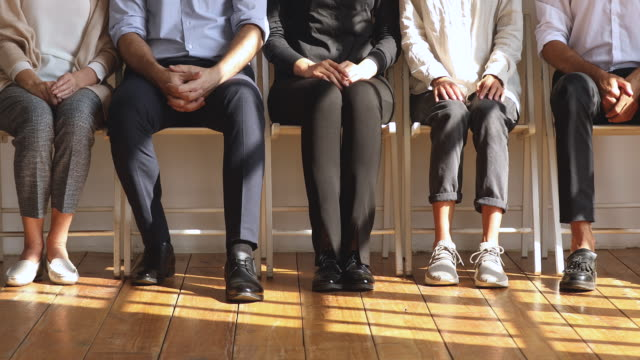 professional unemployed business people sit on chairs, legs closeup view - unemployment stock videos & royalty-free footage