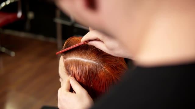 Estilista de pelo profesional irreconocible prepara pelos de mujer para colorear en el estudio de belleza, mujer cambia su mirada, profesional coloración y cuidado del cabello, concepto de belleza. Tiro de cámara lenta - vídeo