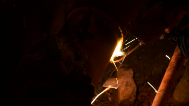 A professional welder of an intervention team welding two heating system pipes together at night video
