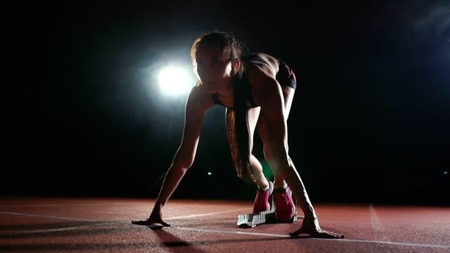 koşu ayakkabıları sprint spor ayakkabı içinde stadyumun parça koyu arka plan üzerinde çalıştırmak için profesyonel kadın atlet karanlık bir arka plan üzerinde - başlama çizgisi stok videoları ve detay görüntü çekimi