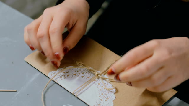 Professional woman decorator working with kraft paper and wrapping envelope video