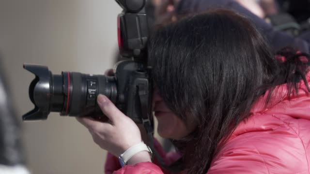 Professional woman photographer with camera taking a picture at an outdoor event video
