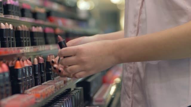 berufstätige frauen kosmetik, wählt käufer girl lippenstift für abend make-up und apply kosmetik einerseits im shopping center - lippenstift stock-videos und b-roll-filmmaterial