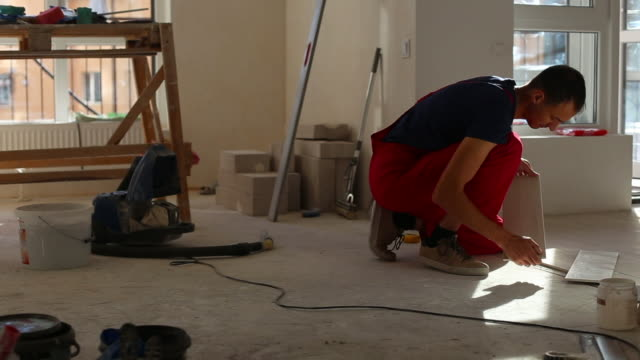 Professional worker laying tiles on floor at construction site close-up slow motion. Builder puts concrete on floor.