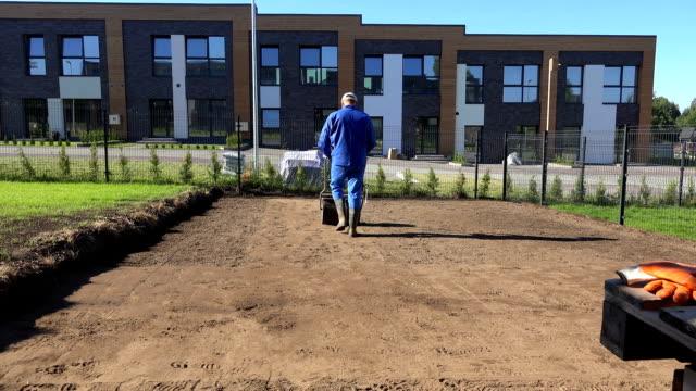 professionell arbetare man kompaktering marken efter gräsmatta seedning sugga. statiskskott - single pampas grass bildbanksvideor och videomaterial från bakom kulisserna