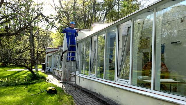 vídeos de stock e filmes b-roll de professional worker on ladder washing glasshouse roof with high pressure tool. - obras em casa janelas