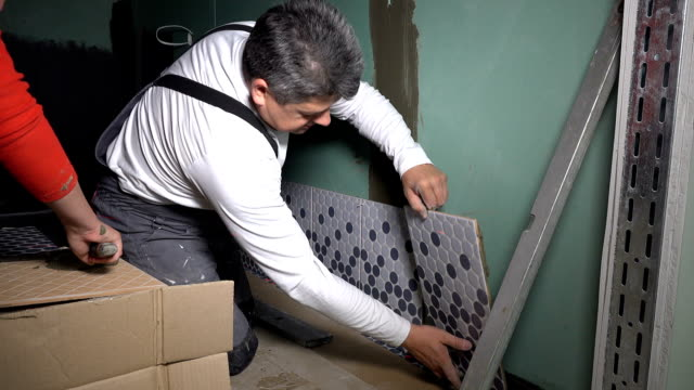 Professional workers install lay tiles on bathroom wall