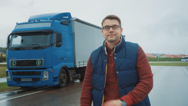 professionell ung lastbilschaufför korsar armar och leenden. bakom honom parkerade blå långdistans-semi-truck med last trailer - biltransporttrailer bildbanksvideor och videomaterial från bakom kulisserna