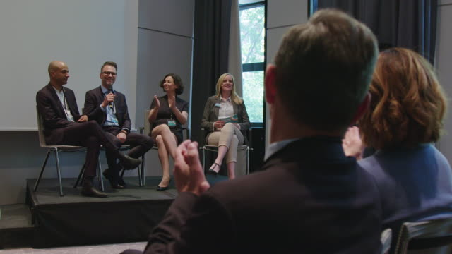 Professionals clapping for businessman at seminar Audience and professionals clapping for businessman during launch event. Executives are sitting in auditorium at hotel during seminar. They are in convention center. conference event stock videos & royalty-free footage