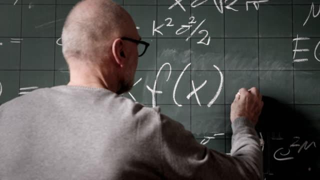Professor writing on blackboard
