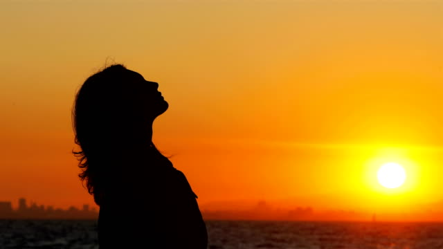 Profile of a woman breathing fresh air at sunset